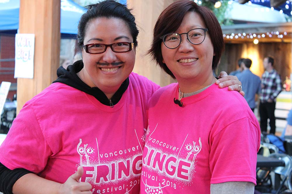 Description: Two people wearing the pink Fringe volunteer t-shirts smile at the camera. The person on the right has drawn a mustache on their face. Caption: Join the Fringe Family (and wear a mustache on September 12 to celebrate Mustache Madness) by signing up to be a volunteer today! Photo by Jenna Owen.